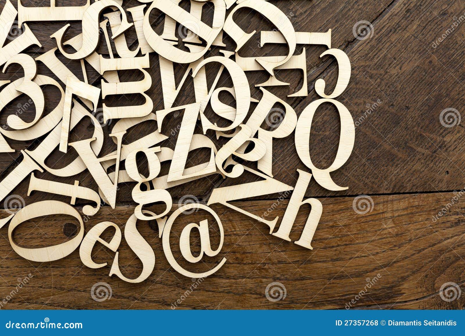 Lettere di legno di alfabeto su vecchia superficie di legno.
