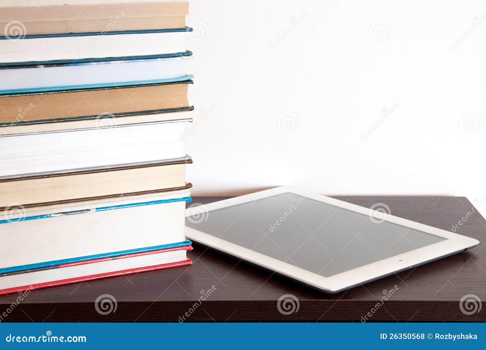 Lettore del E-libro e pila di libri