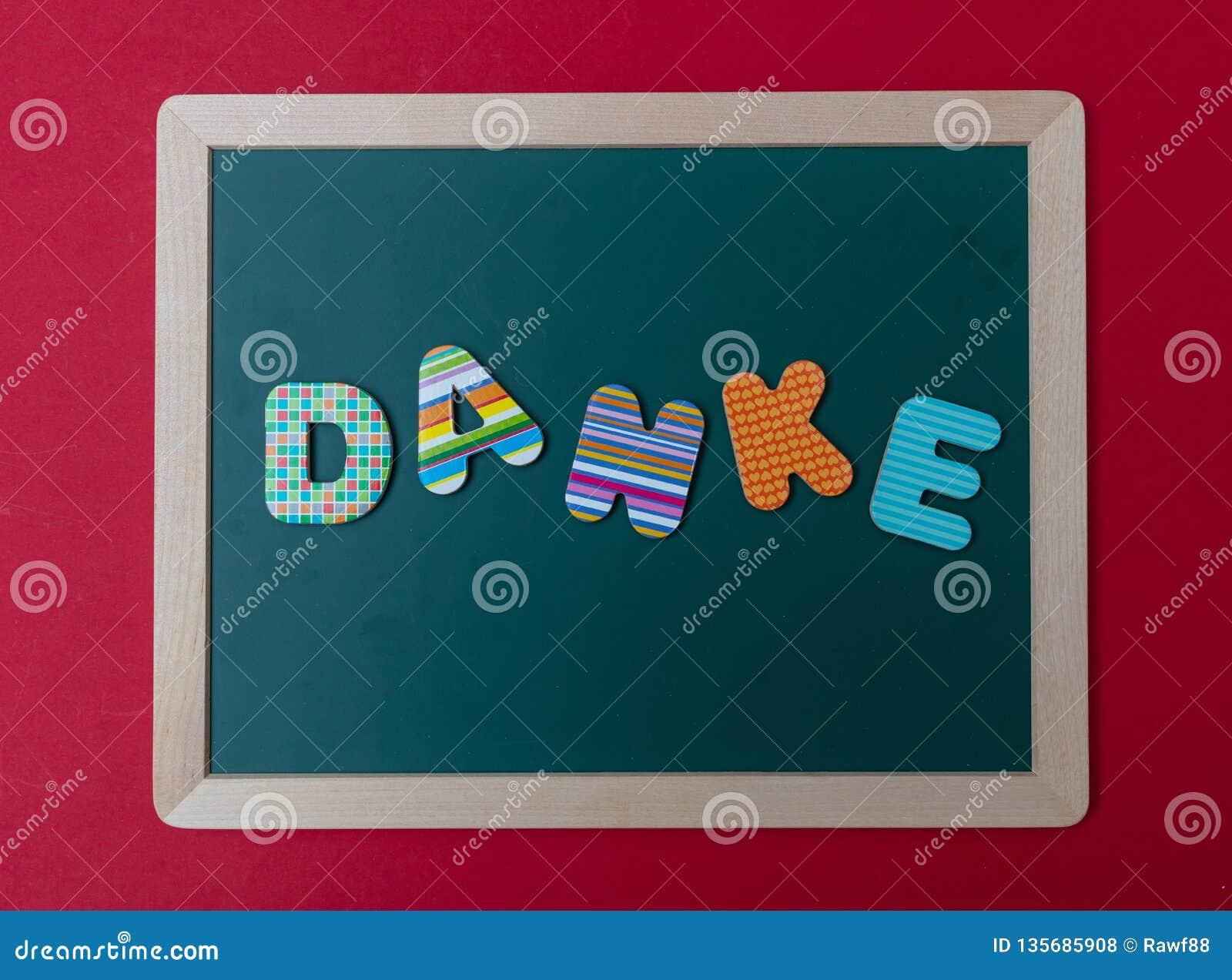 Lettres colorées formant le mot Danke, merci en allemand, sur le conseil vert avec le cadre en bois, fond rouge de mur