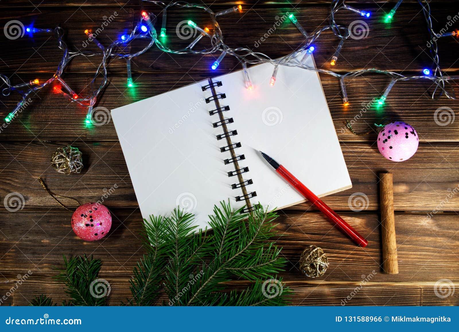 Lettres de calibre avec des salutations de nouvelle année et de Noël ou une liste de cadeaux Le carnet ouvert est localisé sous u