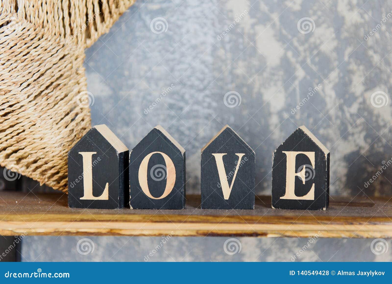 Lettres en bois formant le mot AMOUR écrit sur le fond concret