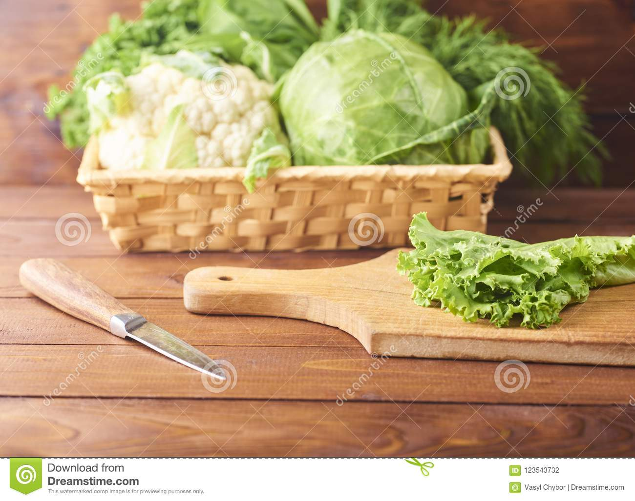 Lettuce leaves on cutting board with knife on wooden background.