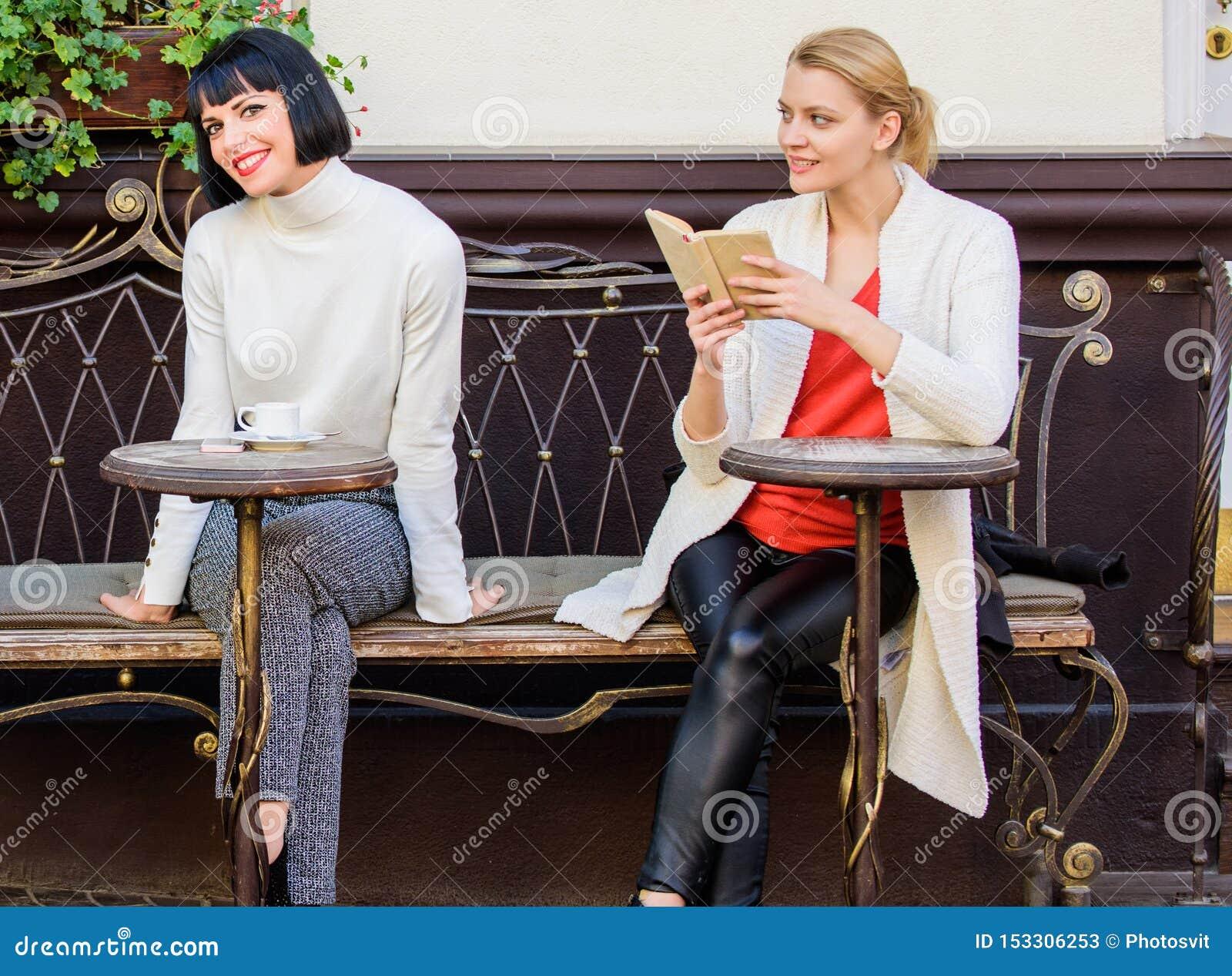 Lettura del libro d ispirazione Amici di ragazze che si siedono il caffè bevente del terrazzo del caffè Letteratura femminile Mig