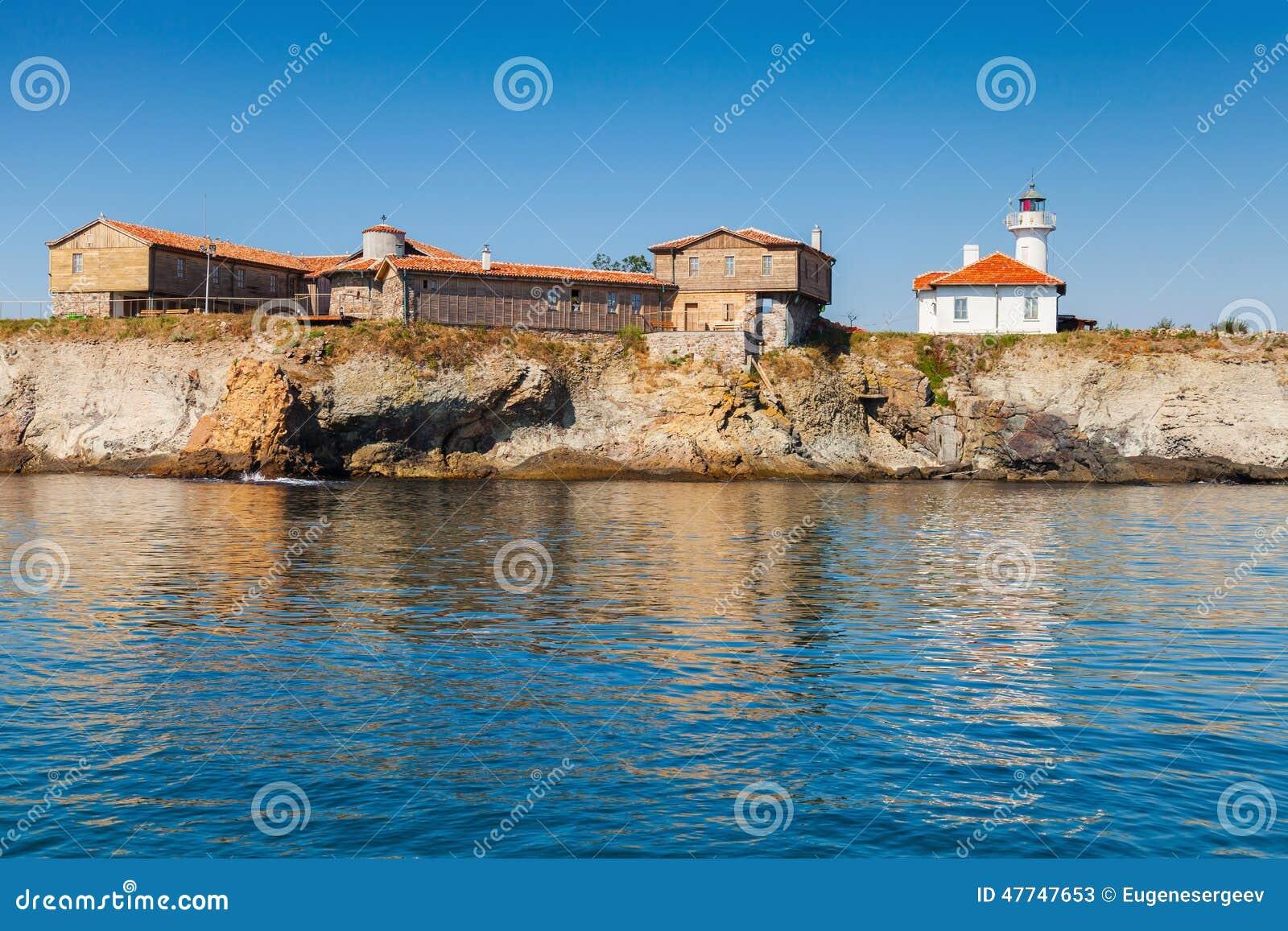 Leuchtturm und alte hölzerne Gebäude auf Insel