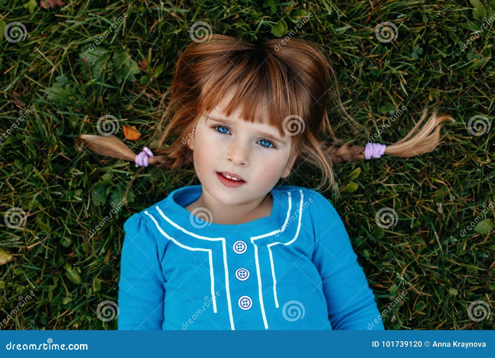 Leuk aanbiddelijk weinig roodharig Kaukasisch meisjeskind in blauwe kleding die in het park van de gebiedsweide buiten liggen
