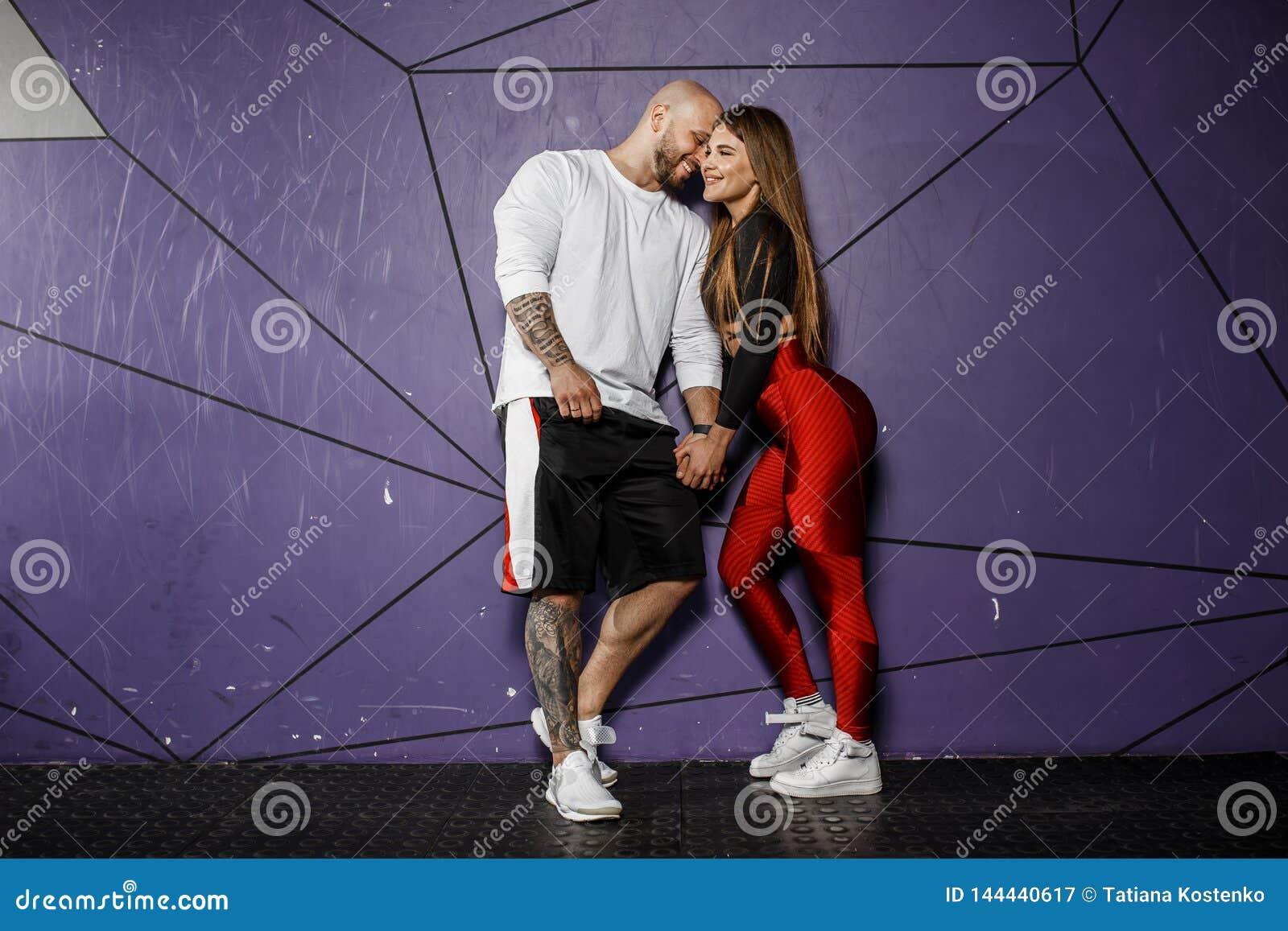 Leuk atletisch paar Het slanke mooie meisje en de sterke atletische mens in sportenkleren koesteren op de achtergrond van