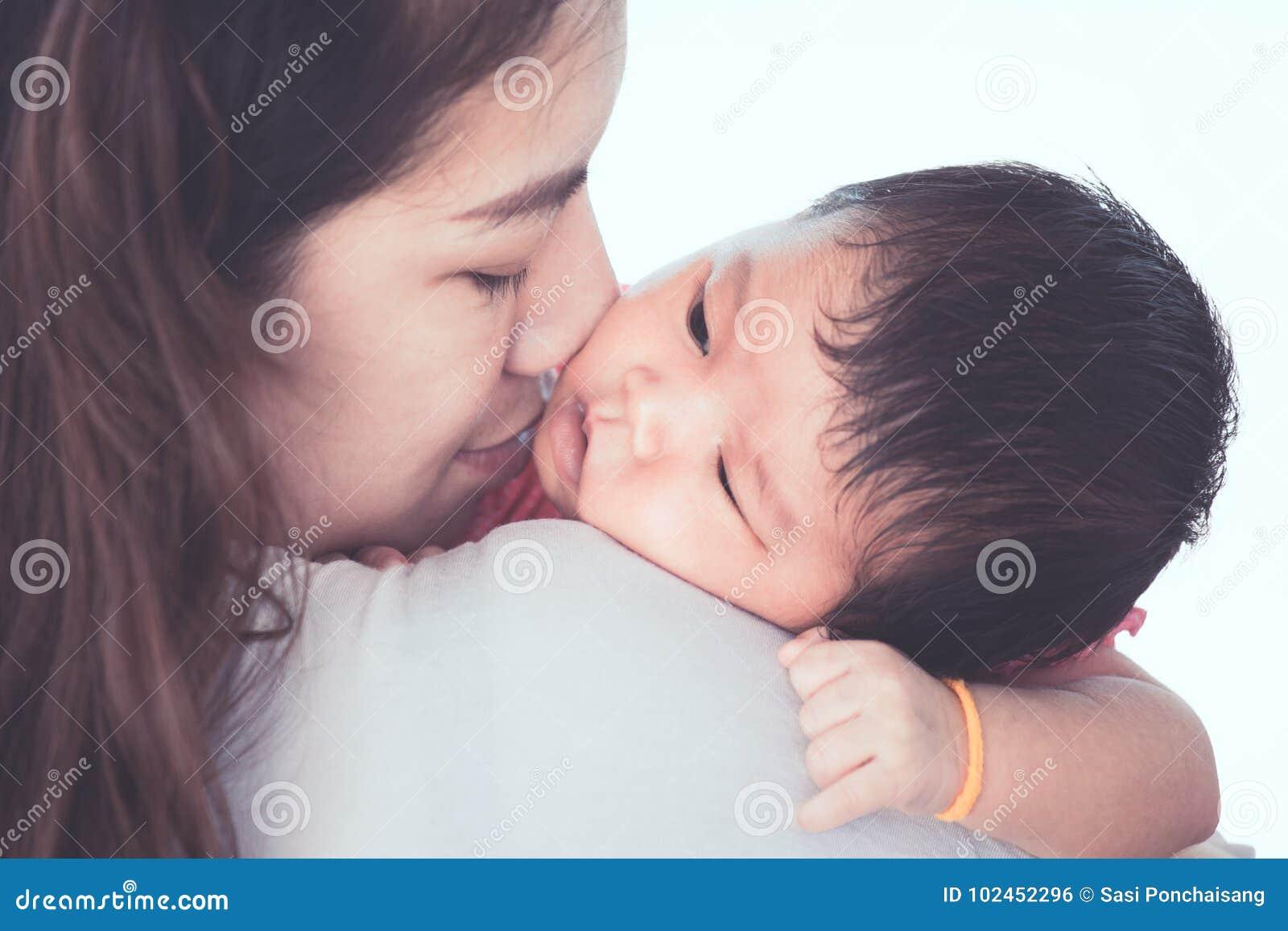 Leuk Aziatisch pasgeboren babymeisje die op moeder` s schouder rusten