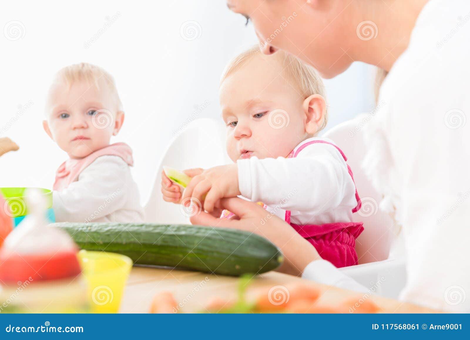 Leuk babymeisje die gezond stevig voedsel in een modern opvangcentrum eten