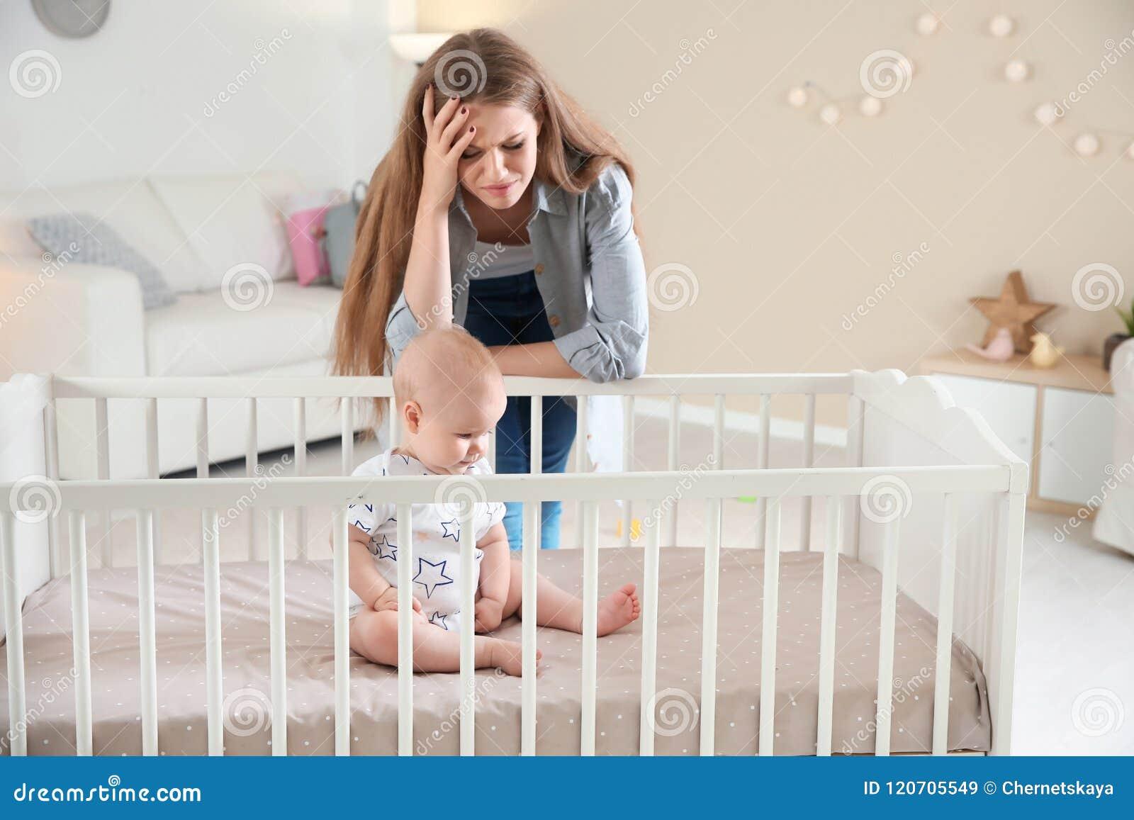 Leuk babymeisje in voederbak en jonge moeder