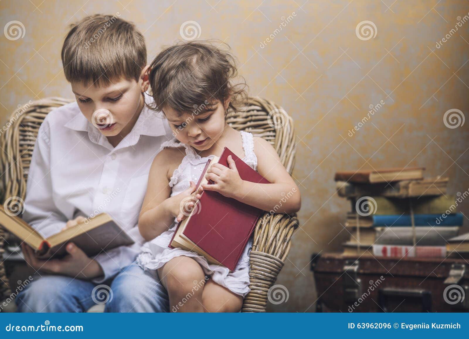 Leuk babysjongen en meisje als voorzitter die een boek in een binnenland lezen