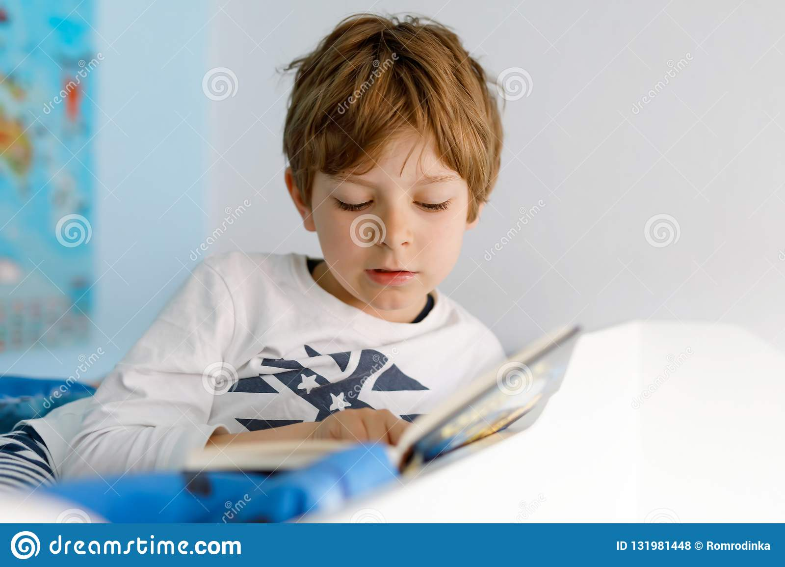Leuk blond weinig jong geitjejongen die in pyjama s boek in zijn slaapkamer lezen Het opgewekte kind luid lezen, zittend in zijn