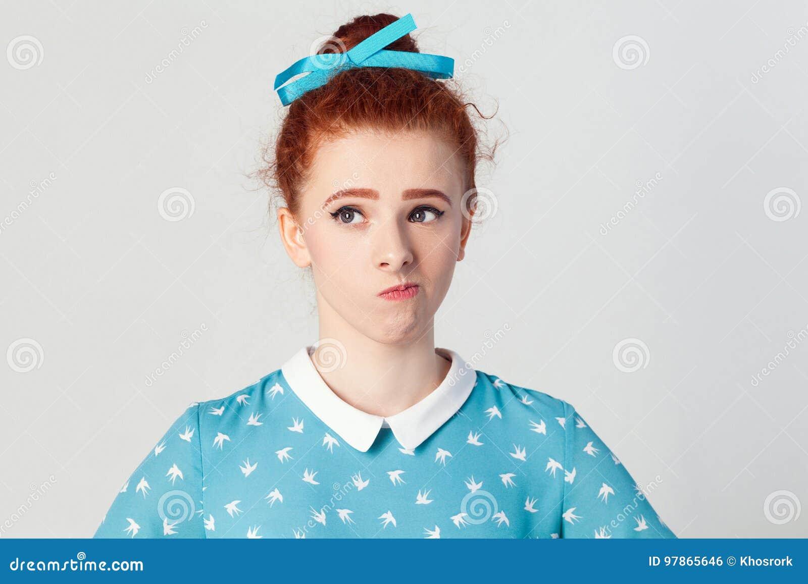 Leuk gembermeisje die, hebbend twijfelachtige en niet afdoende gezichtsuitdrukking, die haar lippen achtervolgen weg kijken