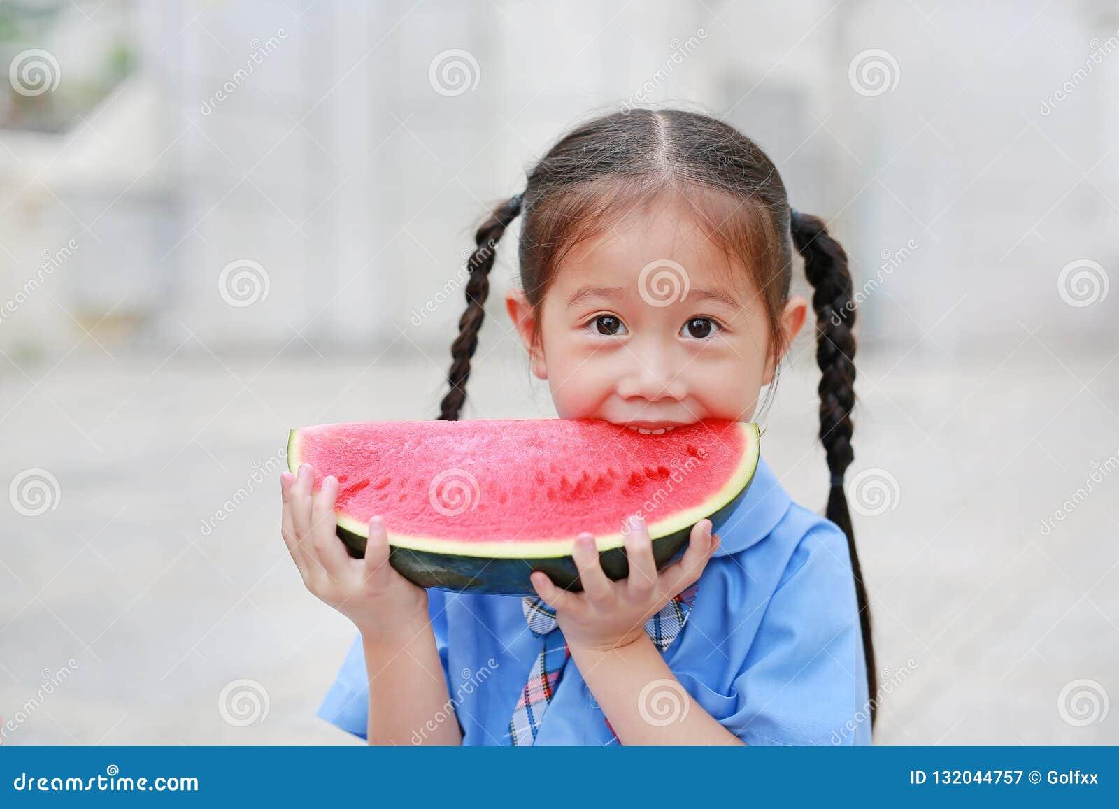 Leuk geniet weinig Aziatisch kindmeisje in eenvormige school het eten van verse gesneden watermeloen