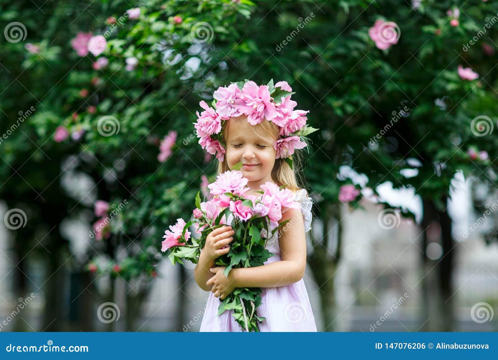Leuk glimlachend meisje met bloemkroon op het park Portret van aanbiddelijk klein jong geitje in openlucht midzomer De Dag van de