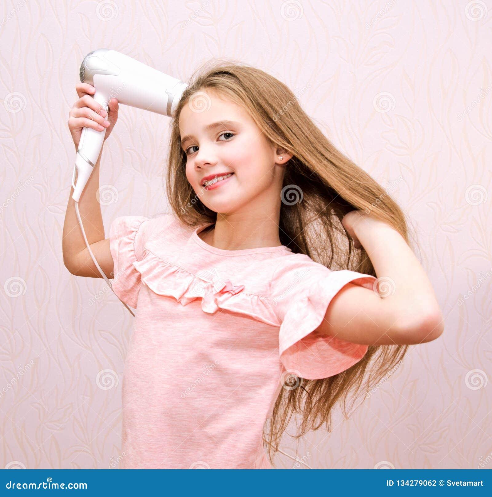 Leuk glimlachend meisjekind die haar lang haar met droogkap drogen