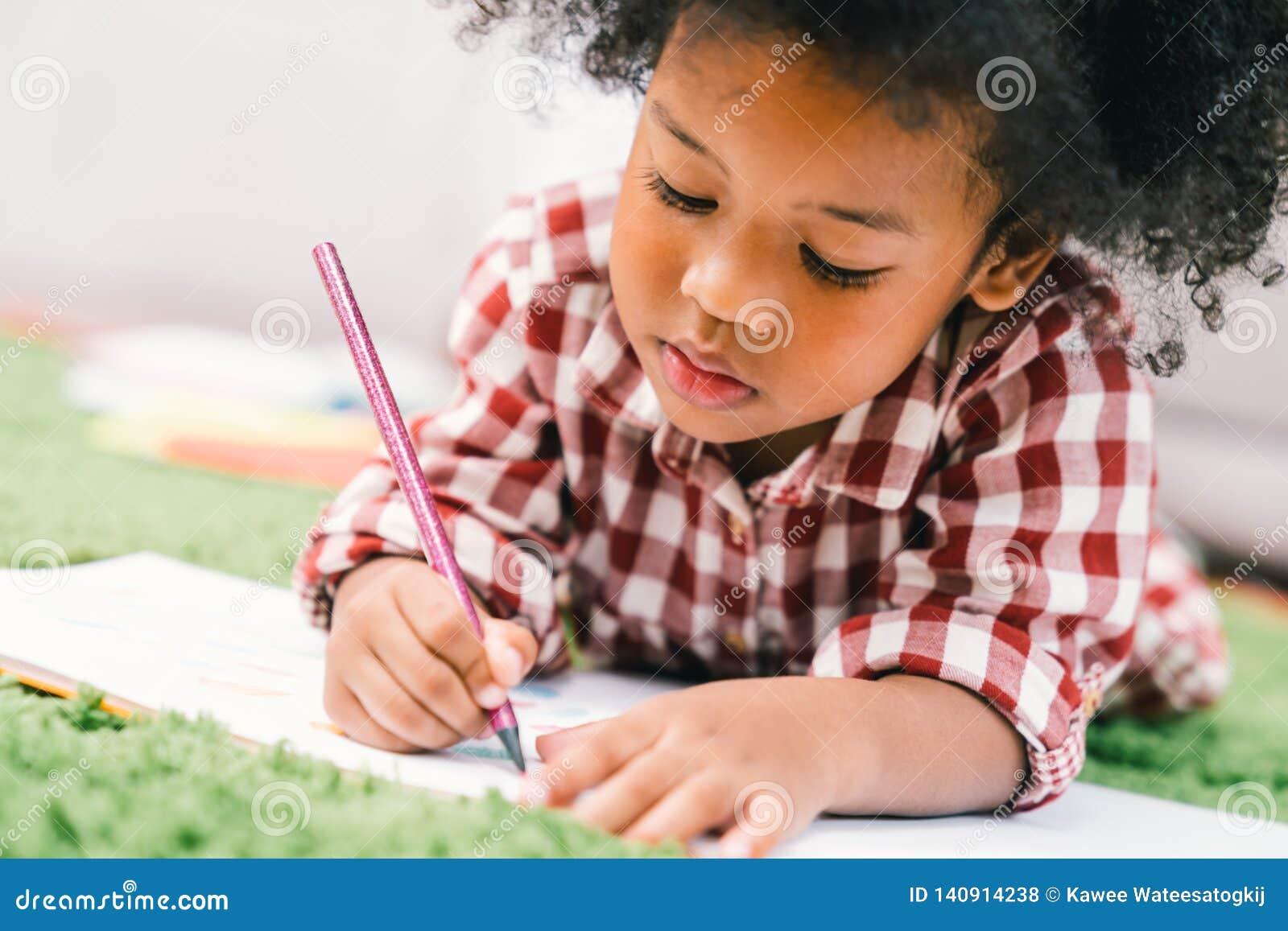 Leuk jong Afrikaans Amerikaans jong geitjemeisje die of met kleurpotlood trekken schilderen