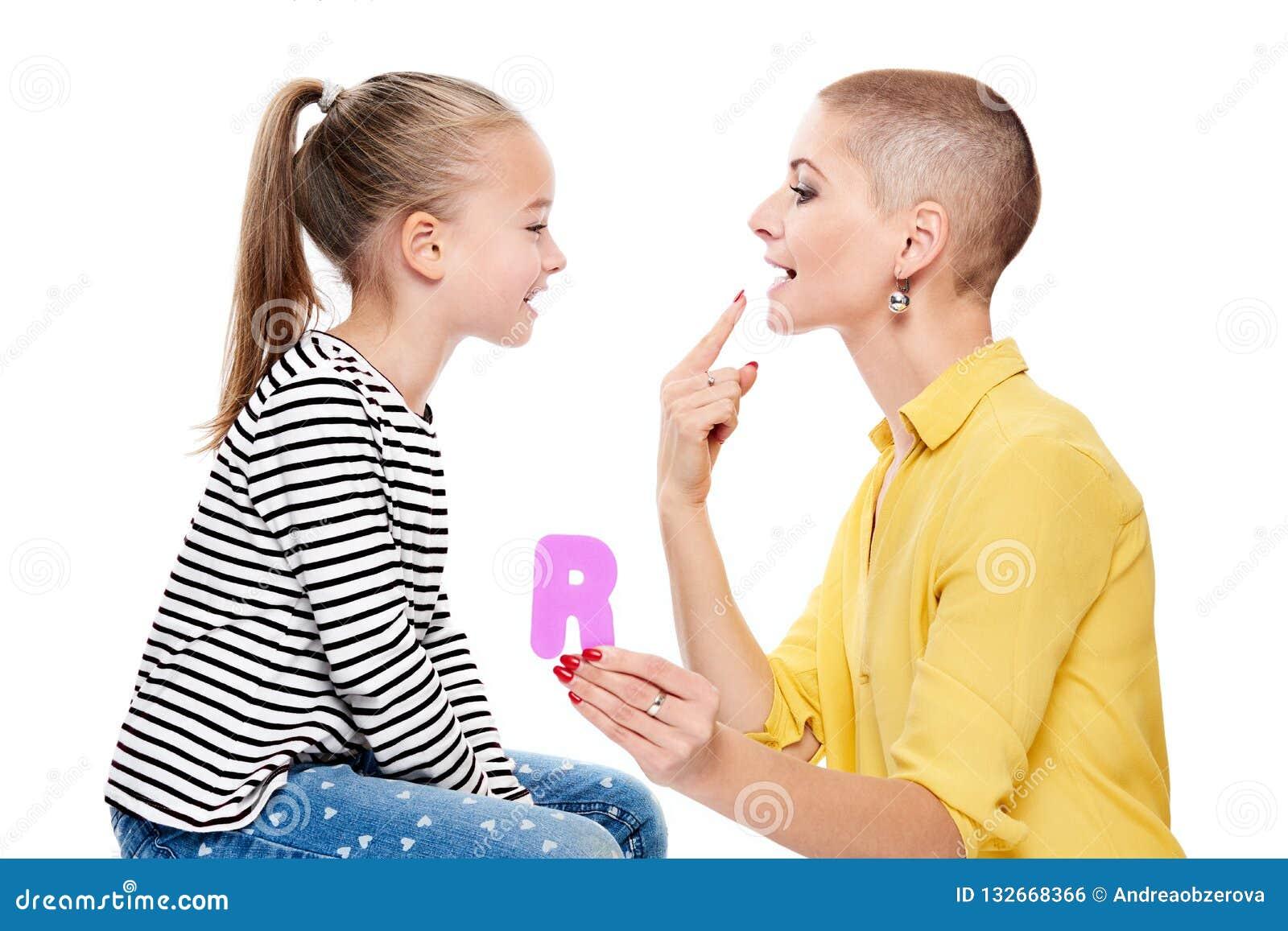 Leuk jong meisje met toespraaktherapeut die correcte uitspraak uitoefenen Het concept van de kindlogopedie op witte achtergrond