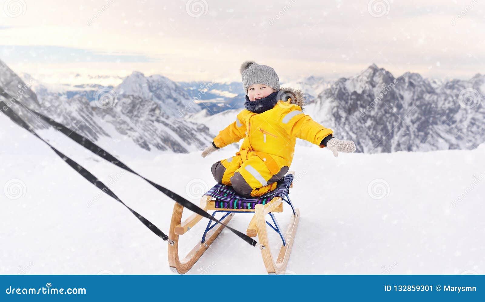 Leuk Kaukasisch weinig jongen die in de bergen van Alpen sledding