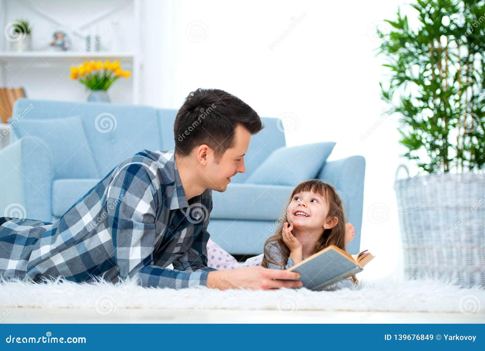 Leuk meisje die aan het sprookje luisteren die van de papalezing op warme vloer samen liggen, het geven het boek van de vaderhold