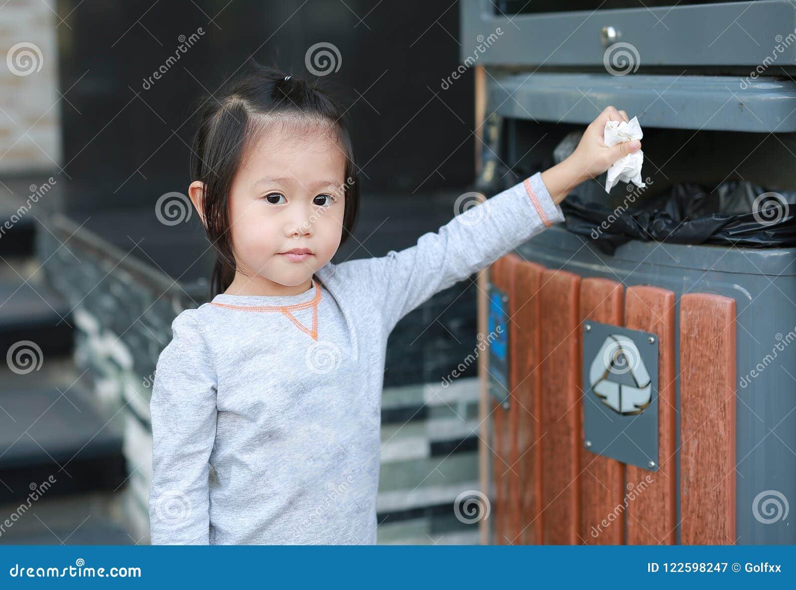 Leuk meisje die afval in de bak zetten openlucht