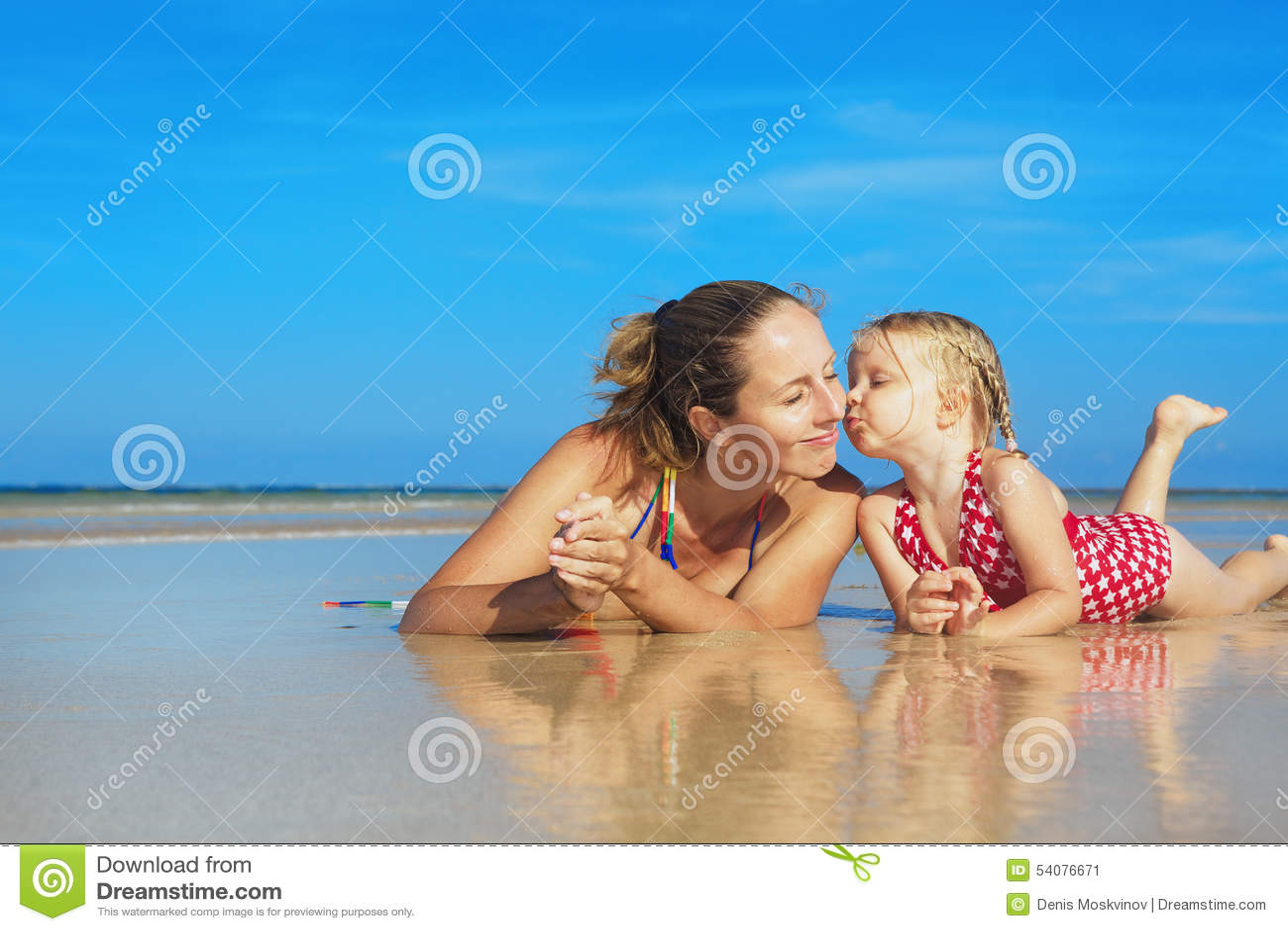 Leuk meisje die gelukkige glimlachende moeder op overzees strand kussen