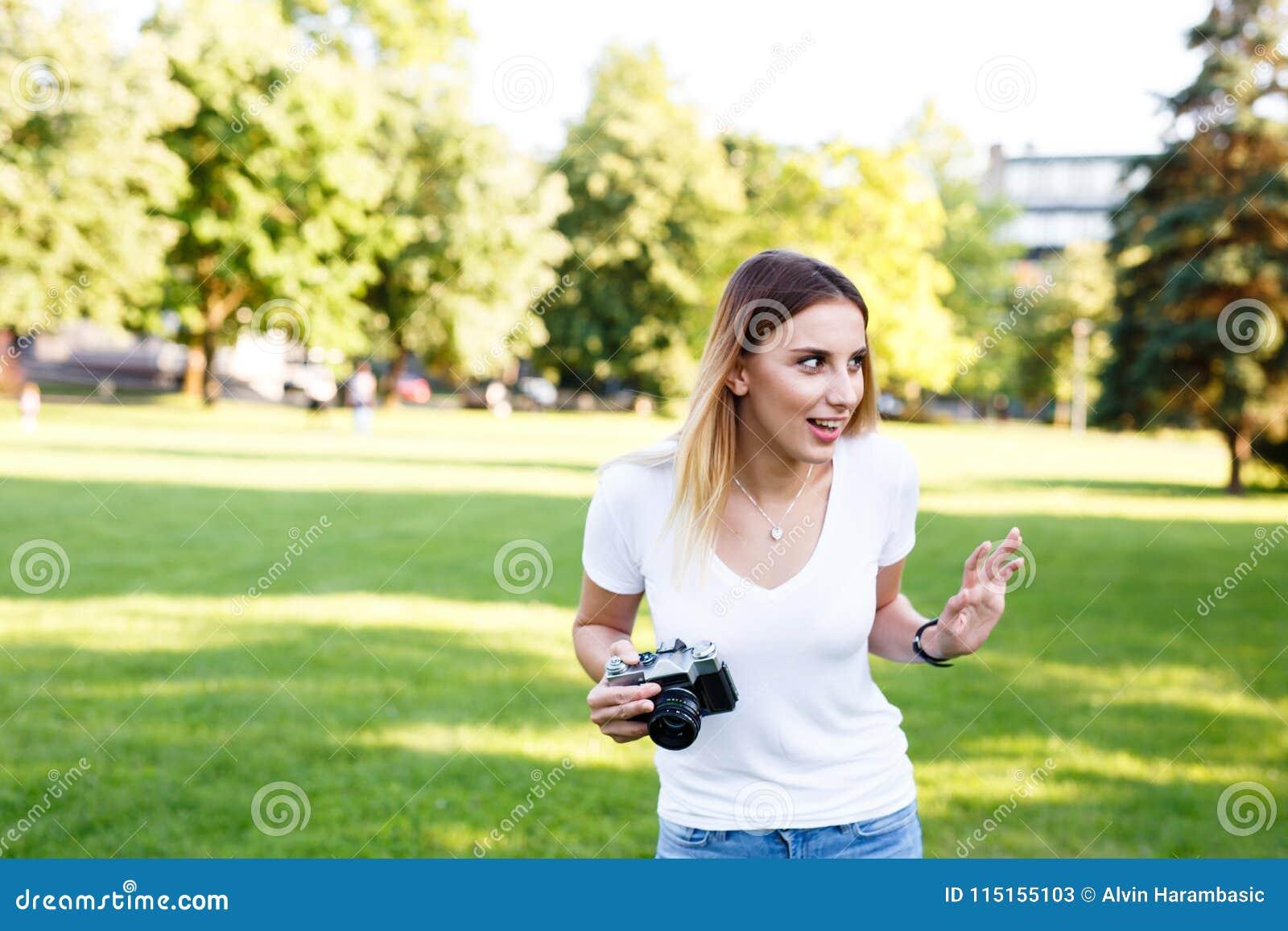 Leuk meisje die op zonnige dag in parkeren met haar camera lopen