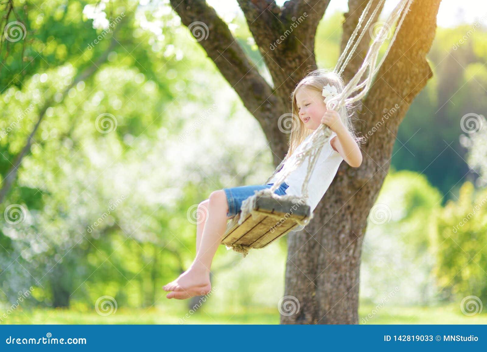 Leuk meisje die pret op een schommeling in de tot bloei komende oude tuin van de appelboom in openlucht op zonnige de lentedag he