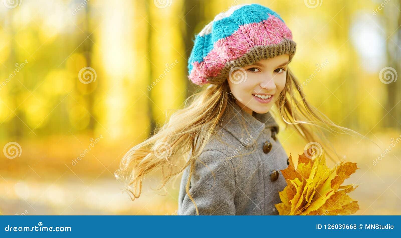 Leuk meisje die pret op mooie de herfstdag hebben Het gelukkige kind spelen in de herfstpark Jong geitje die geel dalingsgeblader