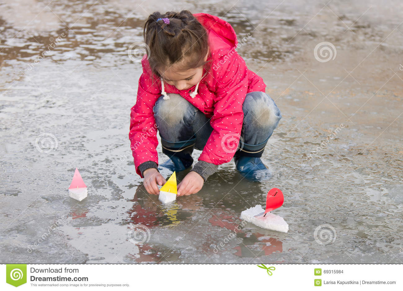 Leuk meisje die in regenlaarzen met schepen in de bronwatervulklei spelen