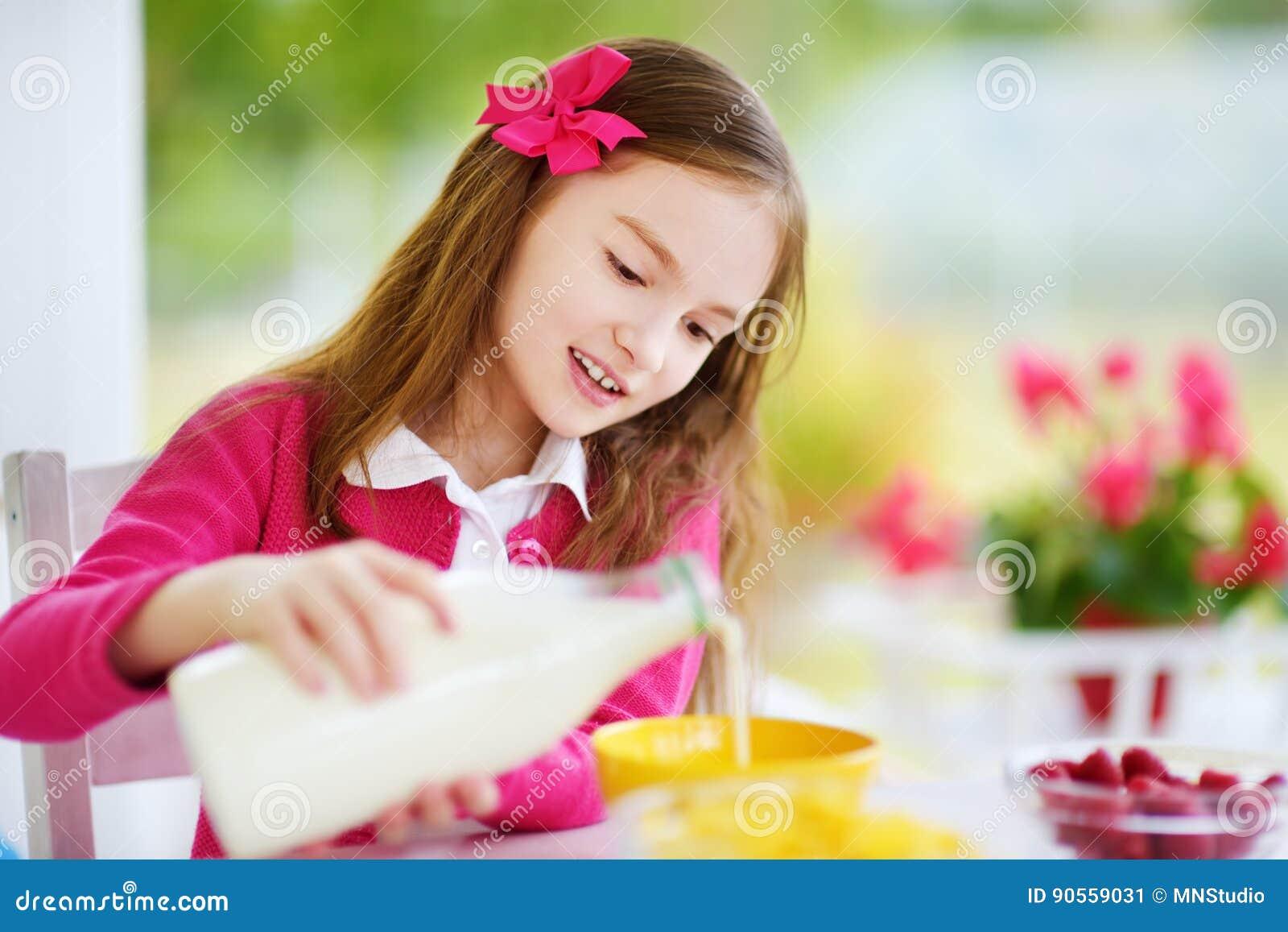 Leuk meisje die van haar ontbijt thuis genieten Mooi kind cornflakes en frambozen eten en consumptiemelk die voor school