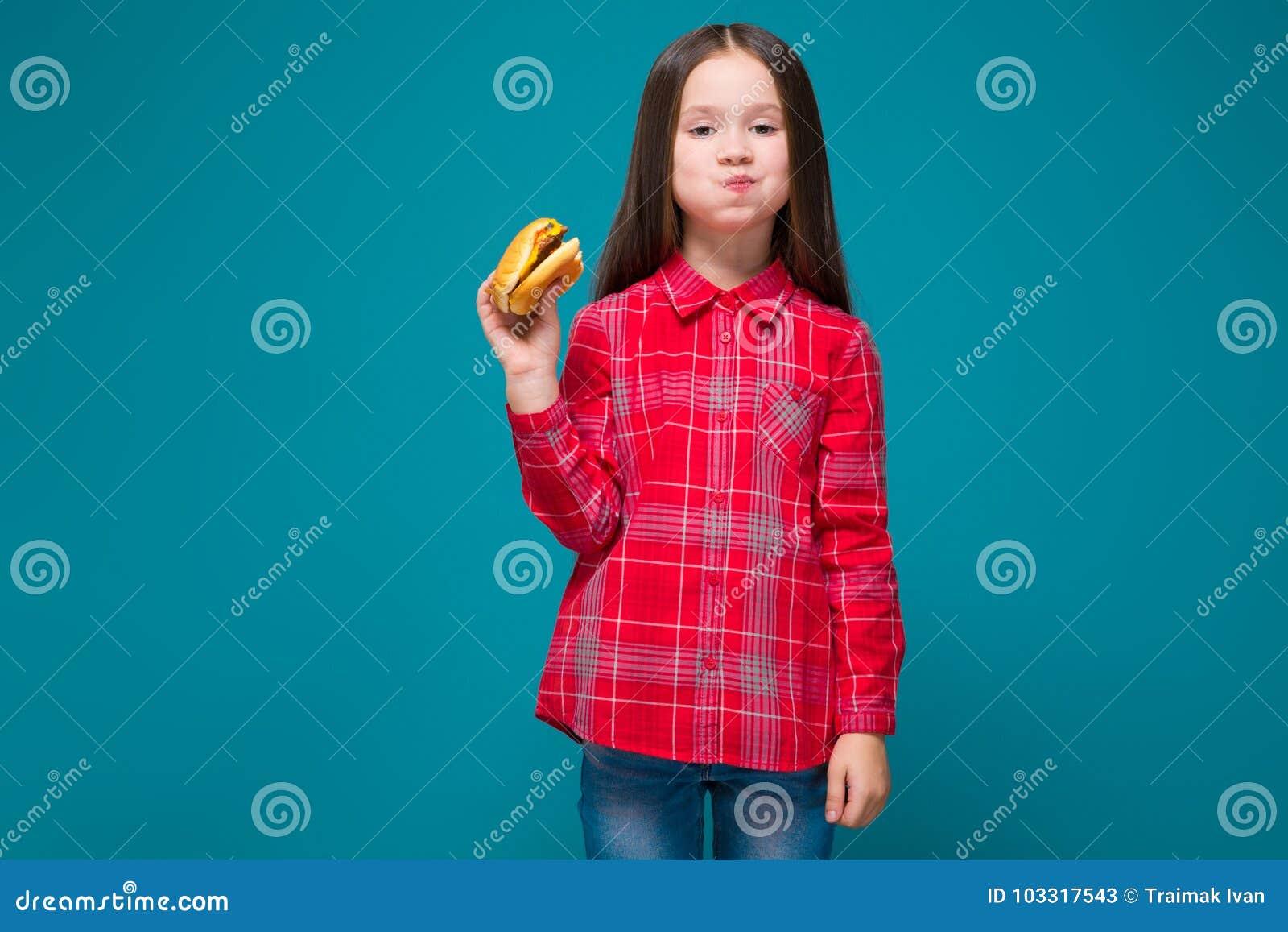 Leuk meisje in geruit overhemd met de donkerbruine hamburger van de haargreep