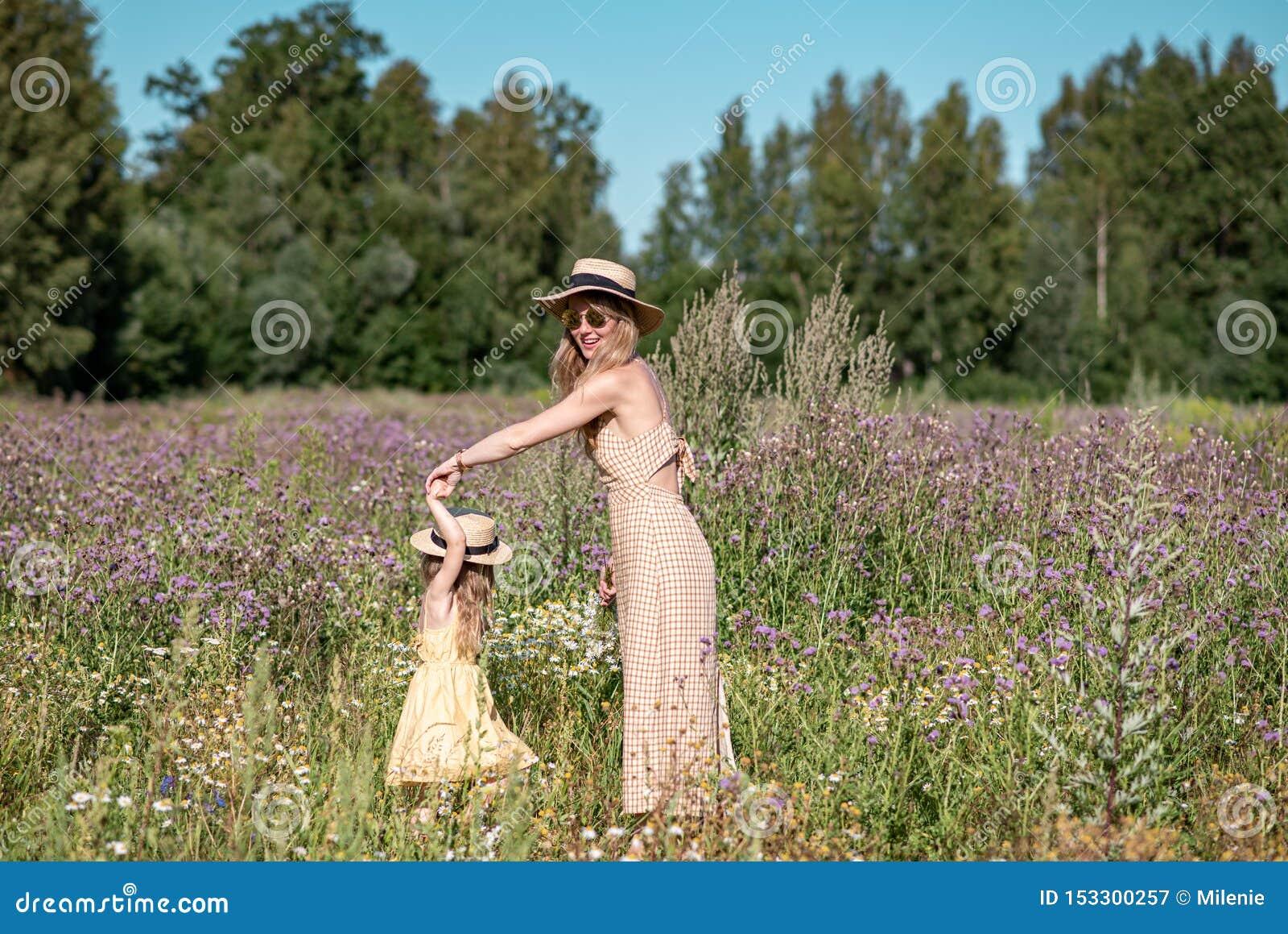 Leuk meisje met haar moeder die op het bloemengebied lopen