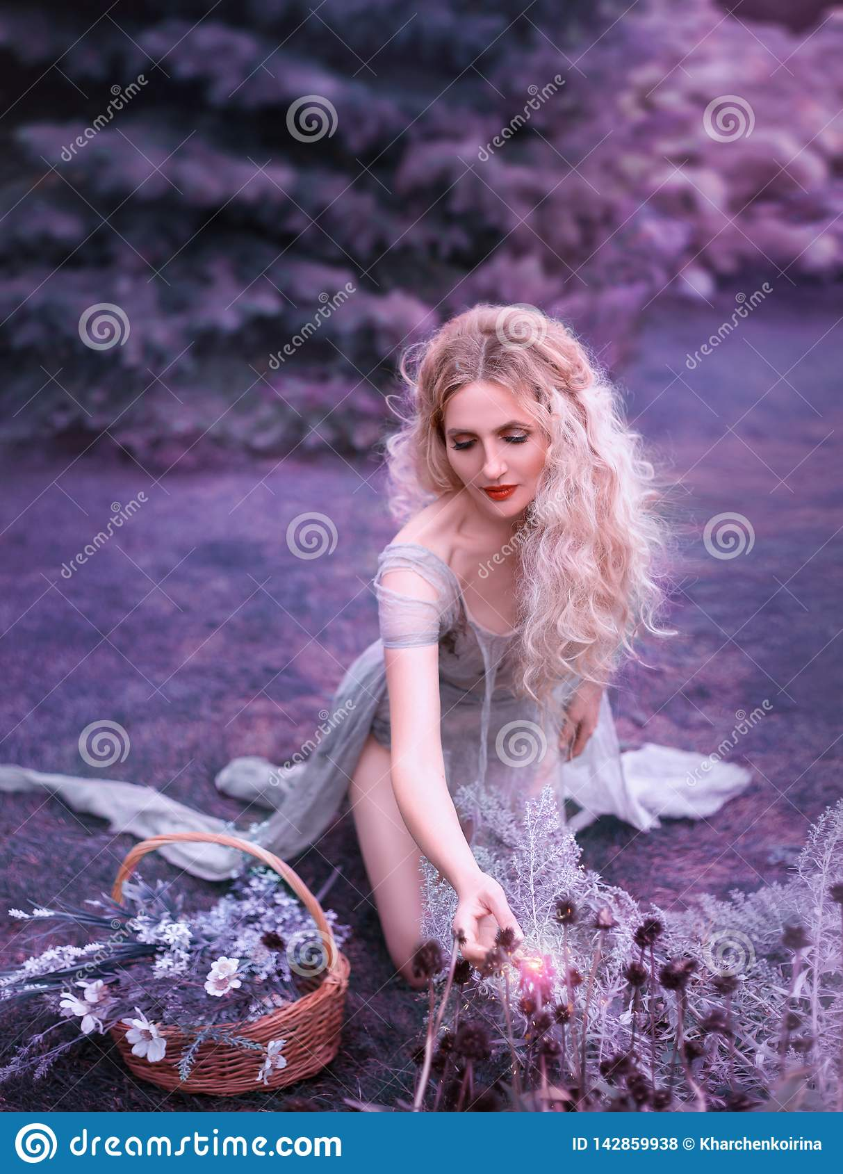 Leuk meisje in oude grijze kleding met lange besnoeiingstrein en open benen die op knieën zitten en wilde geheimzinnige bloemen v