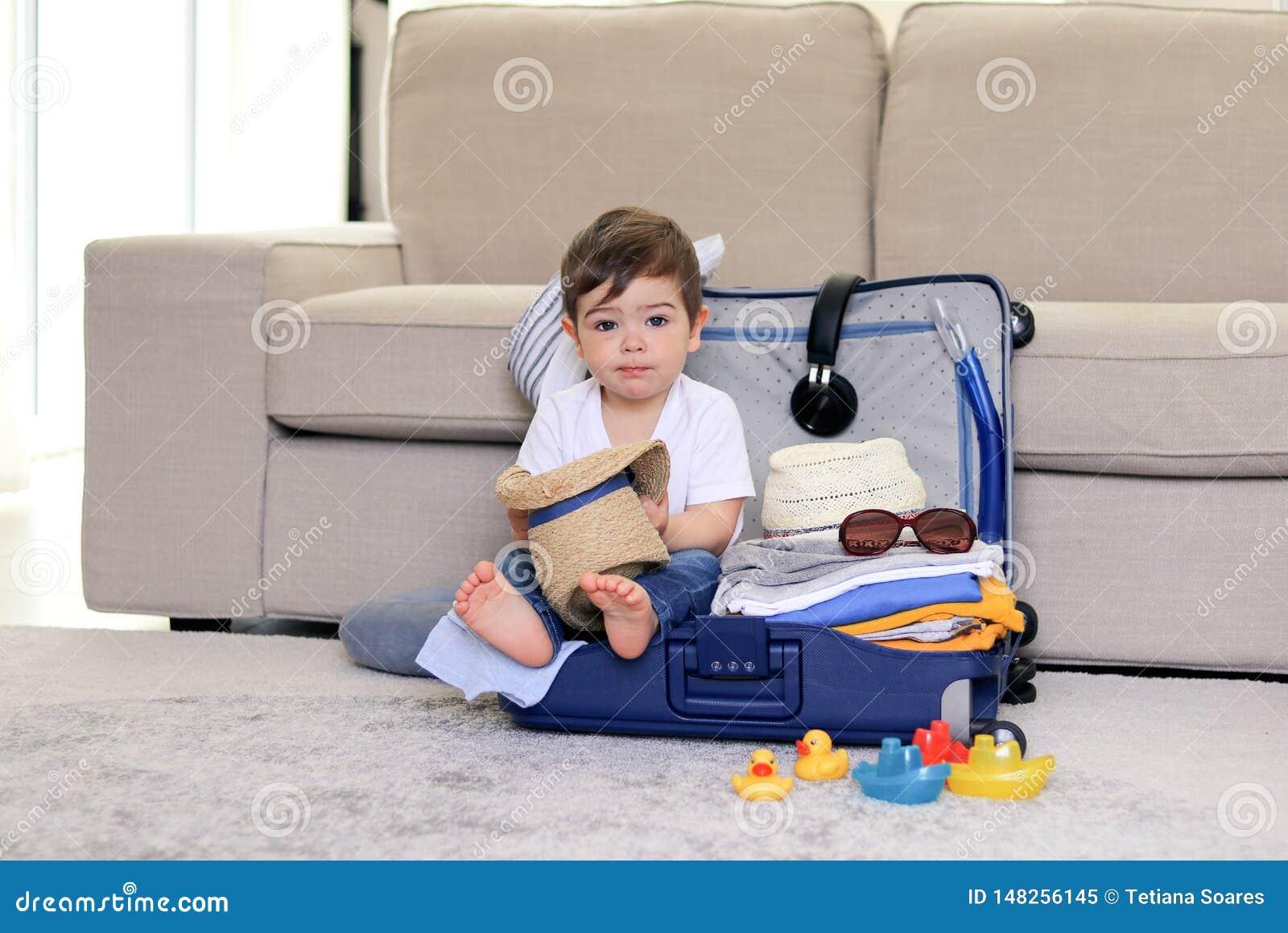Leuk pakte weinig babyjongen met de grappige zitting van de gezichtsuitdrukking in blauwe het strohoed van de kofferholding in ha
