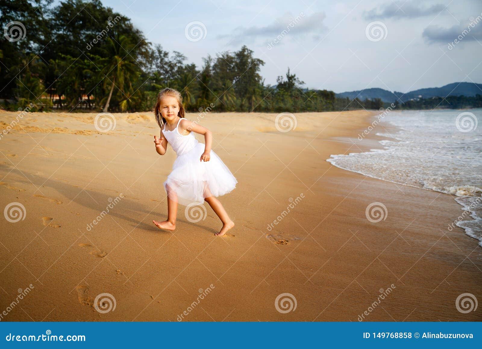 Leuk peutermeisje met blondehaar in een witte tutukleding die op een zandig strand bij zonsondergang lopen Gelukkig kinderjarenge