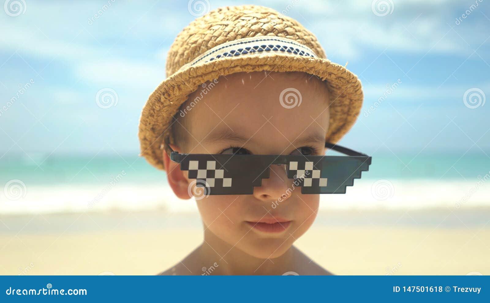 Leuk portret van weinig jongen in strohoed met zonnebril die zich op de zomerstrand bevinden