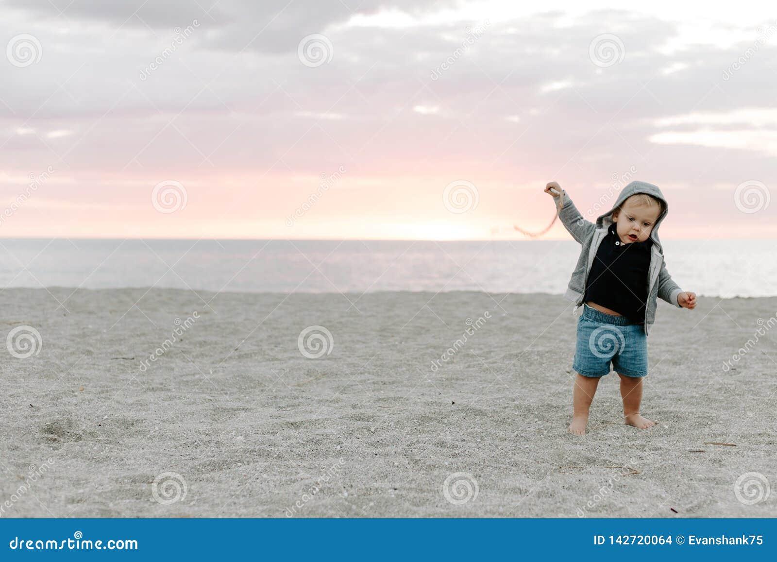 Leuk portret van Weinig Kind die van de Babyjongen en in het Zand bij het Strand tijdens Zonsondergang buiten op Vakantie in Hood