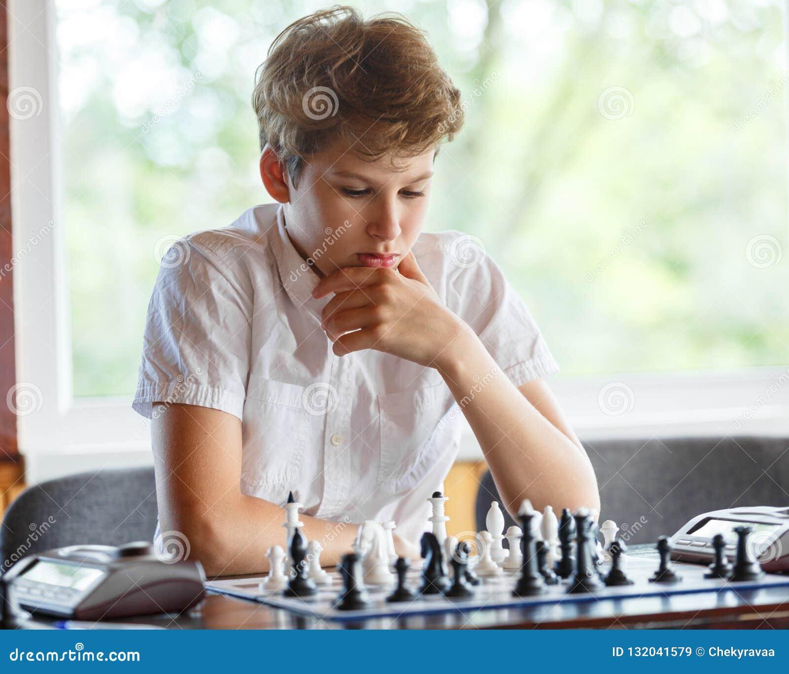 Leuk, slim, zit 11 jaar oude jongens in wit overhemd in het klaslokaal en speelt schaak op het schaakbord Opleiding, les, hobby