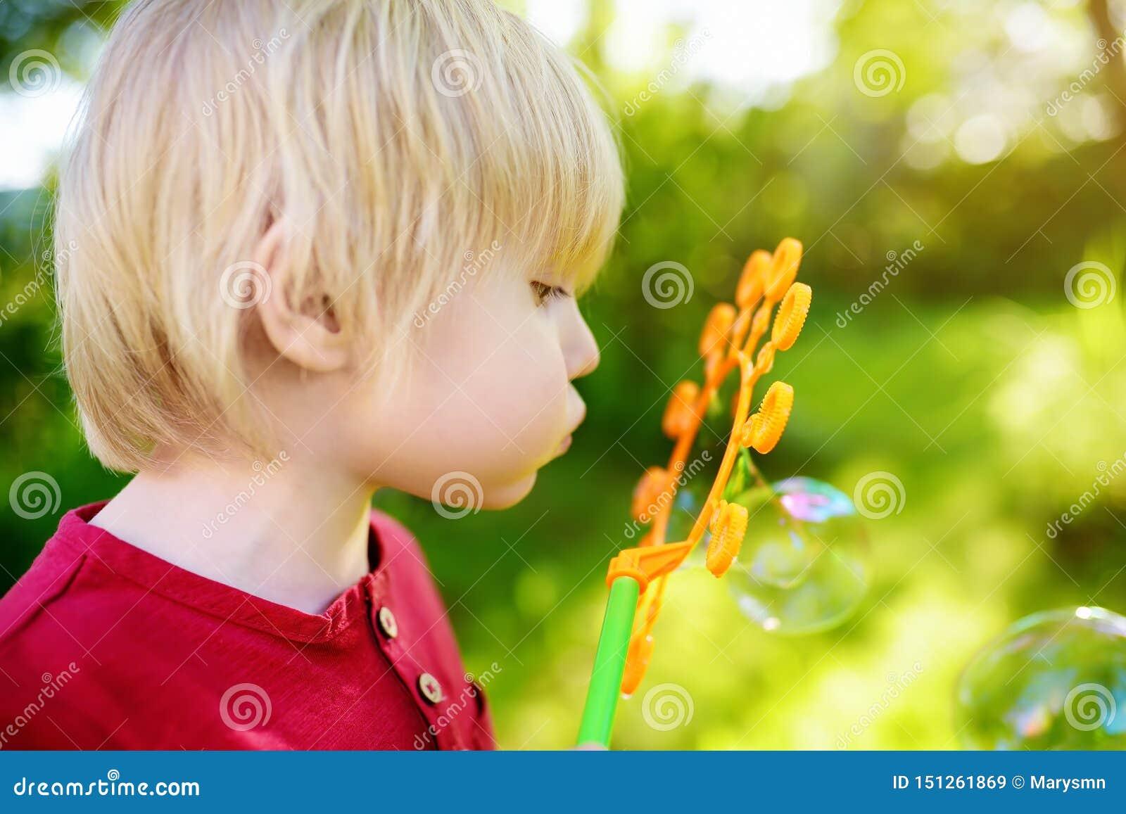 Leuk speelt weinig jongen met grote bellen openlucht Het kind blaast gelijktijdig grote en kleine bellen