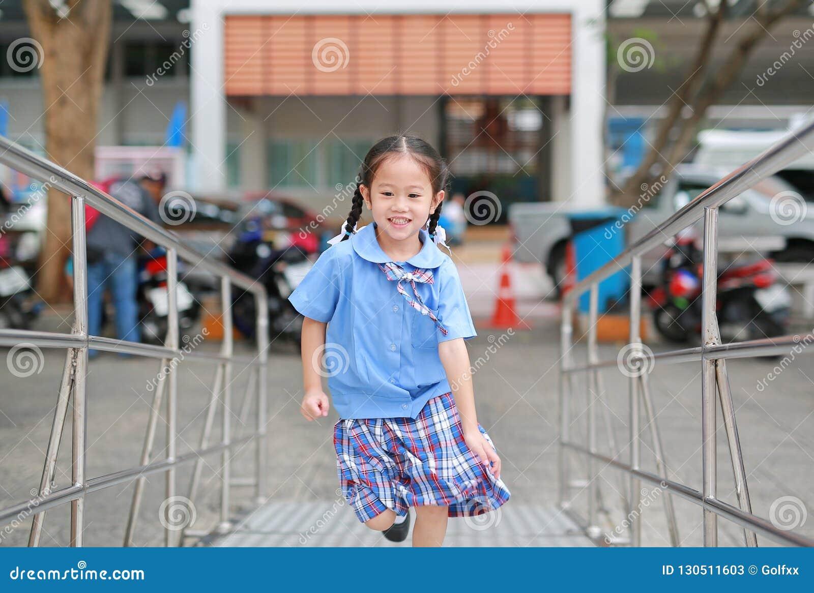 Leuk weinig Aziatisch kindmeisje in school eenvormige het lanceren metaaltrede