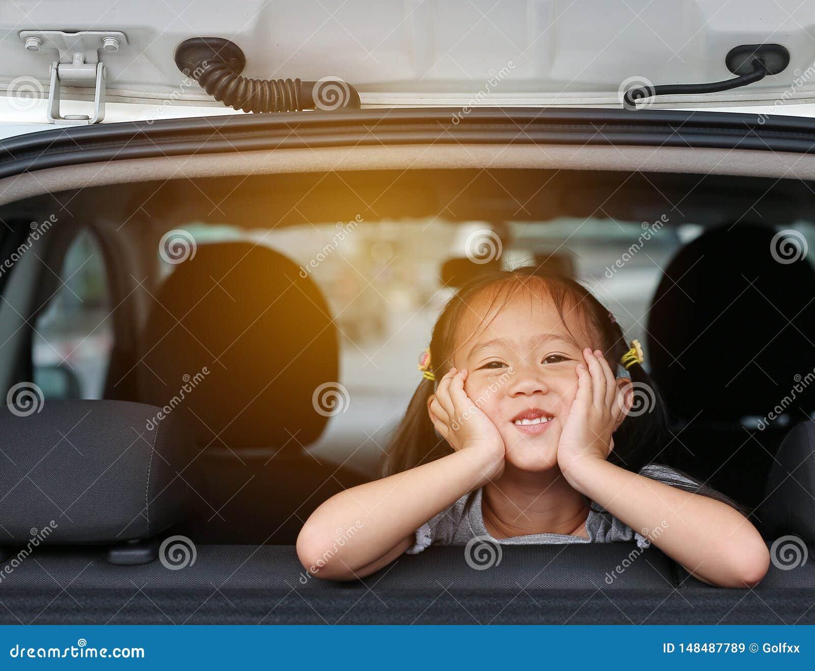 Leuk weinig Aziatisch meisje die camera van het venster van de auto met stralen van zonlicht kijken