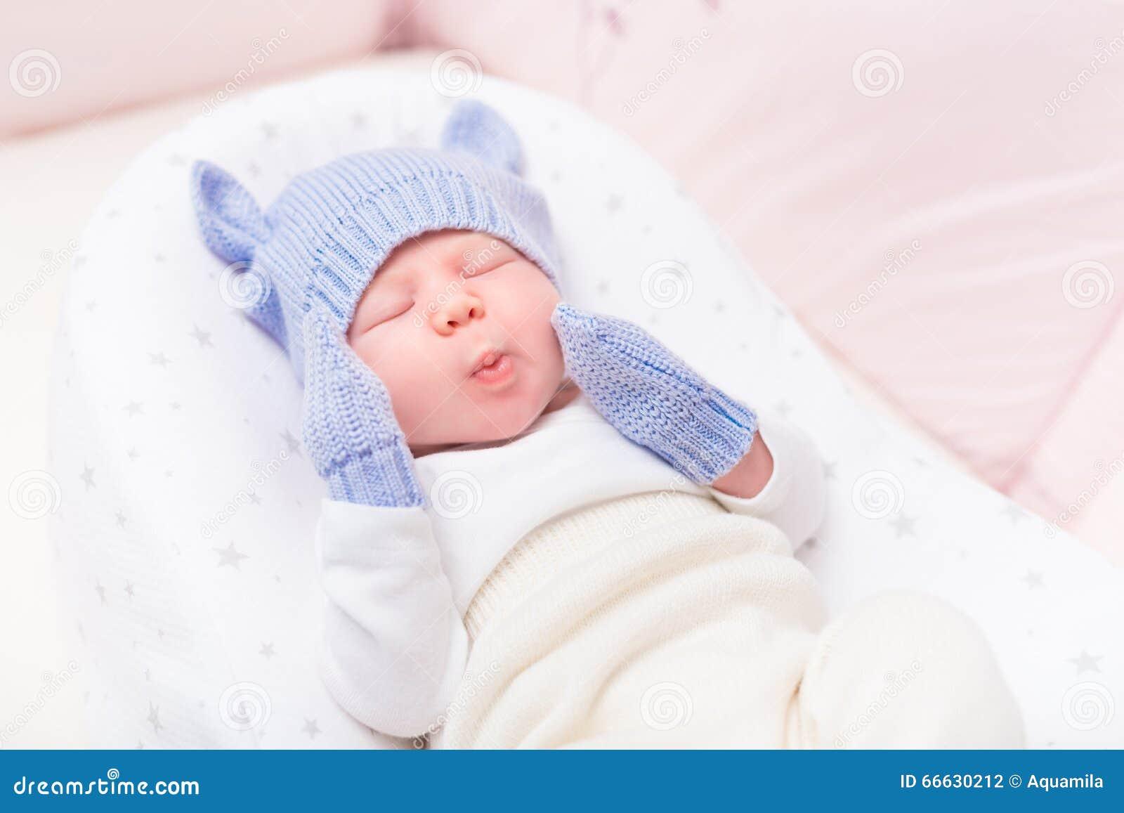Leuk weinig baby die gebreide blauwe hoed met oren en vuisthandschoenen dragen