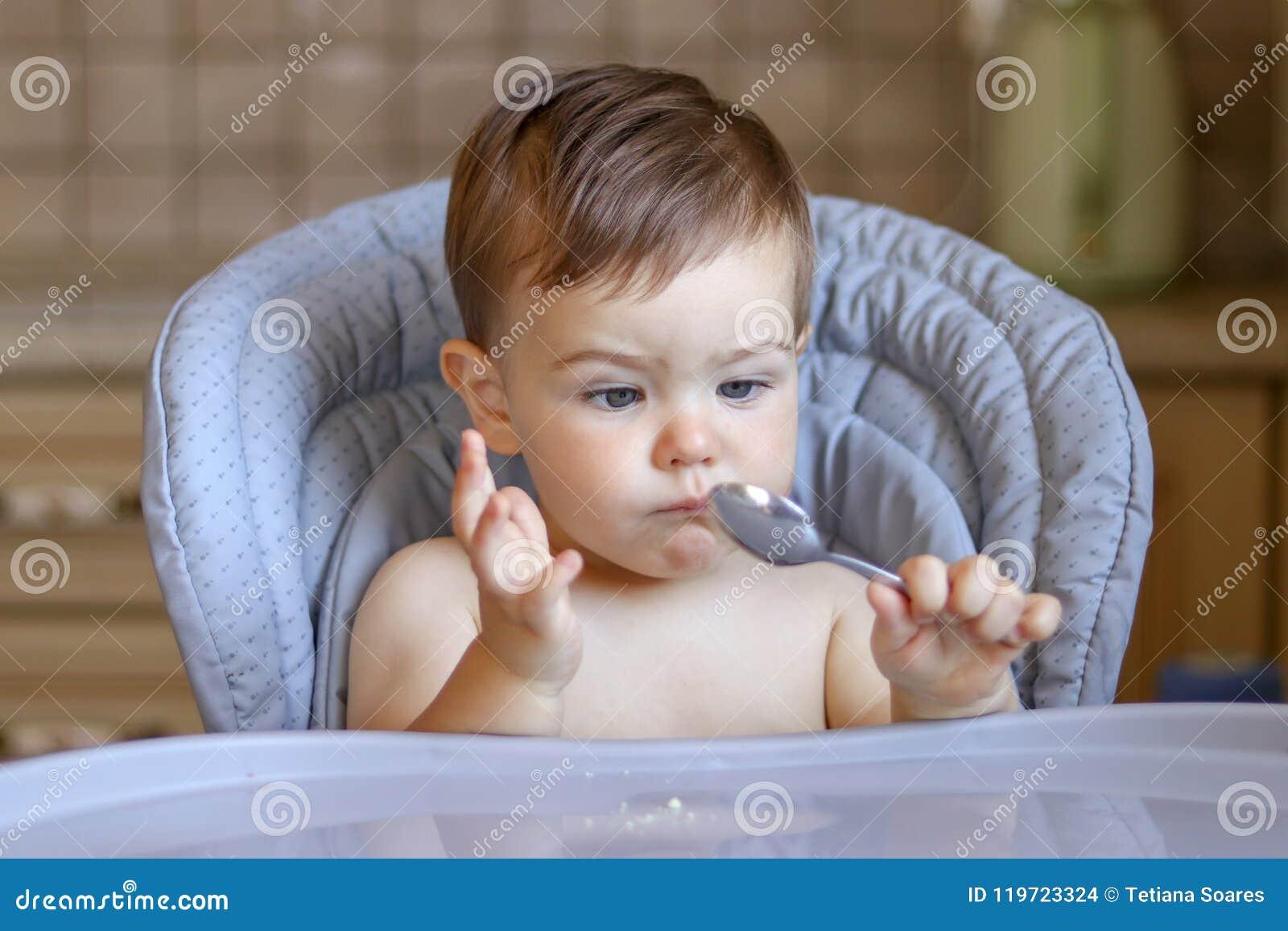 Leuk weinig babyjongen die lepel in zijn hand met grappige verbijsterde gezichtsuitdrukking bekijken