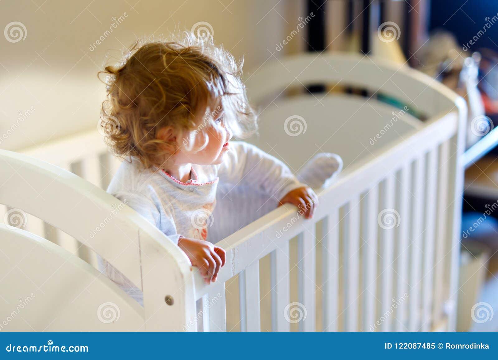 Leuk weinig babymeisje die in wieg na slaap liggen Gezond gelukkig kind die in bed uit beklimmen