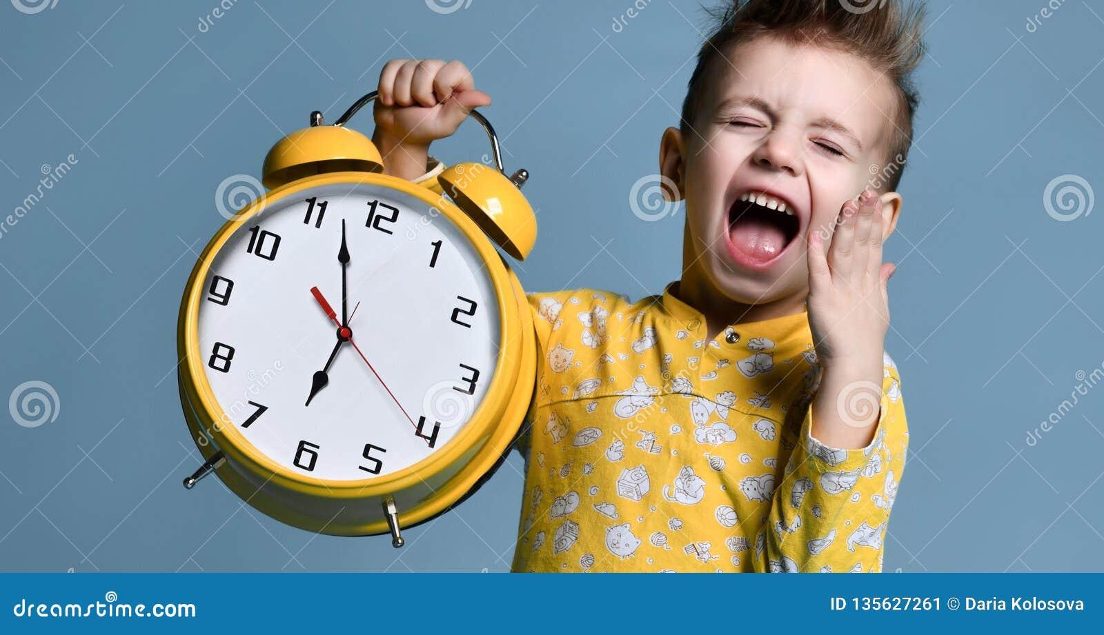 Leuk weinig die jongen met wekker, op blauw wordt geïsoleerd Grappig jong geitje die op wekker op 7 uur op ochtend richten