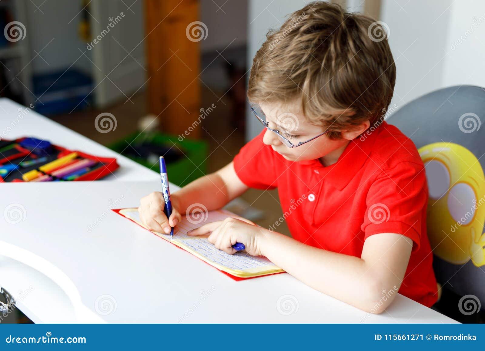 Leuk weinig jong geitjejongen met glazen die thuis thuiswerk maken, schrijvend brieven met kleurrijke pennen