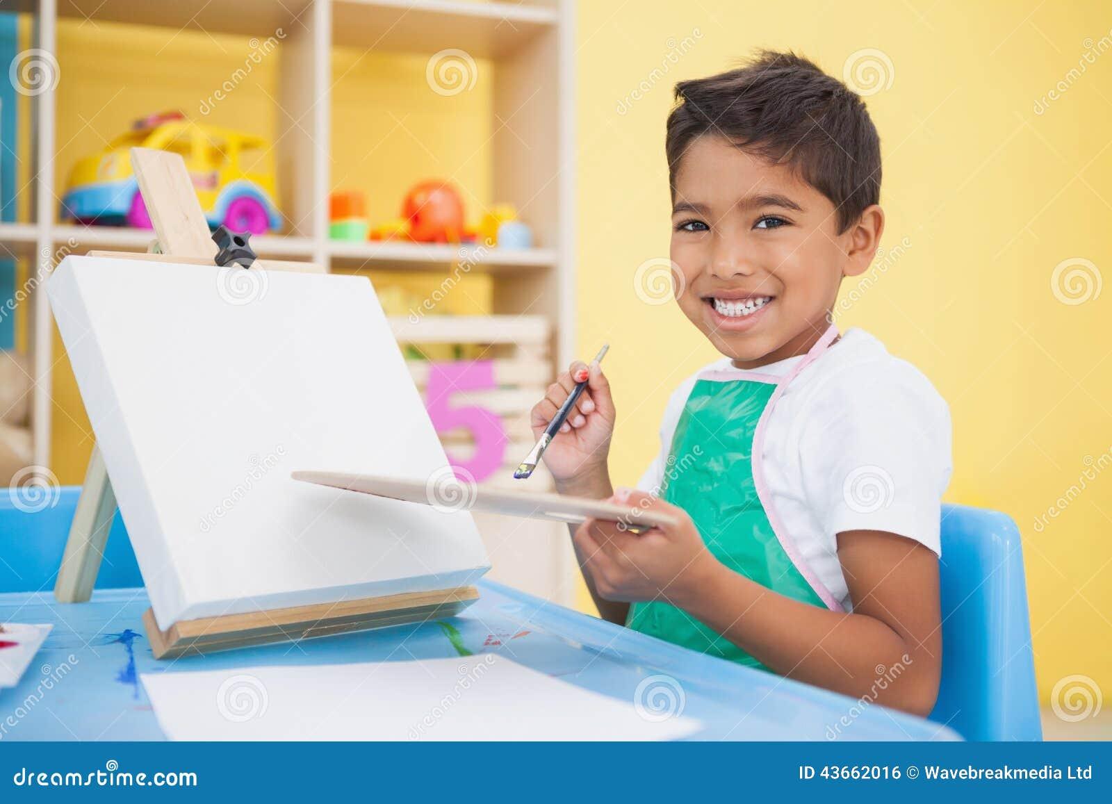 Leuk weinig jongen die bij lijst in klaslokaal schilderen stock foto afbeelding 43662016 - Schilderen kind jongen ...