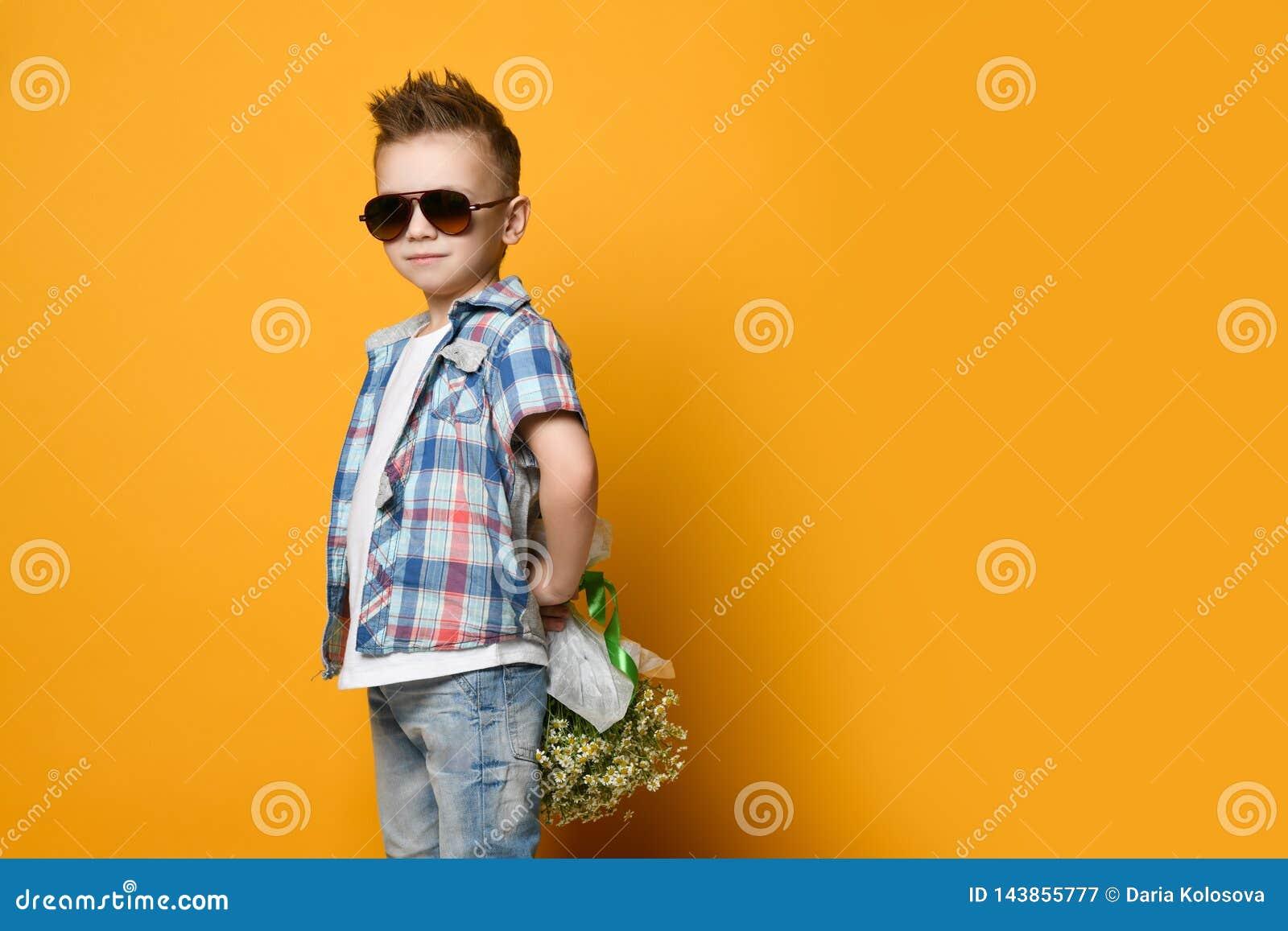 Leuk weinig jongen die een boeket van bloemen houden