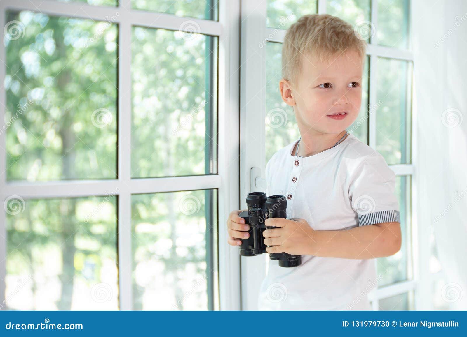 Leuk weinig jongen die zwarte binoculair houden en vanaf de camera kijken