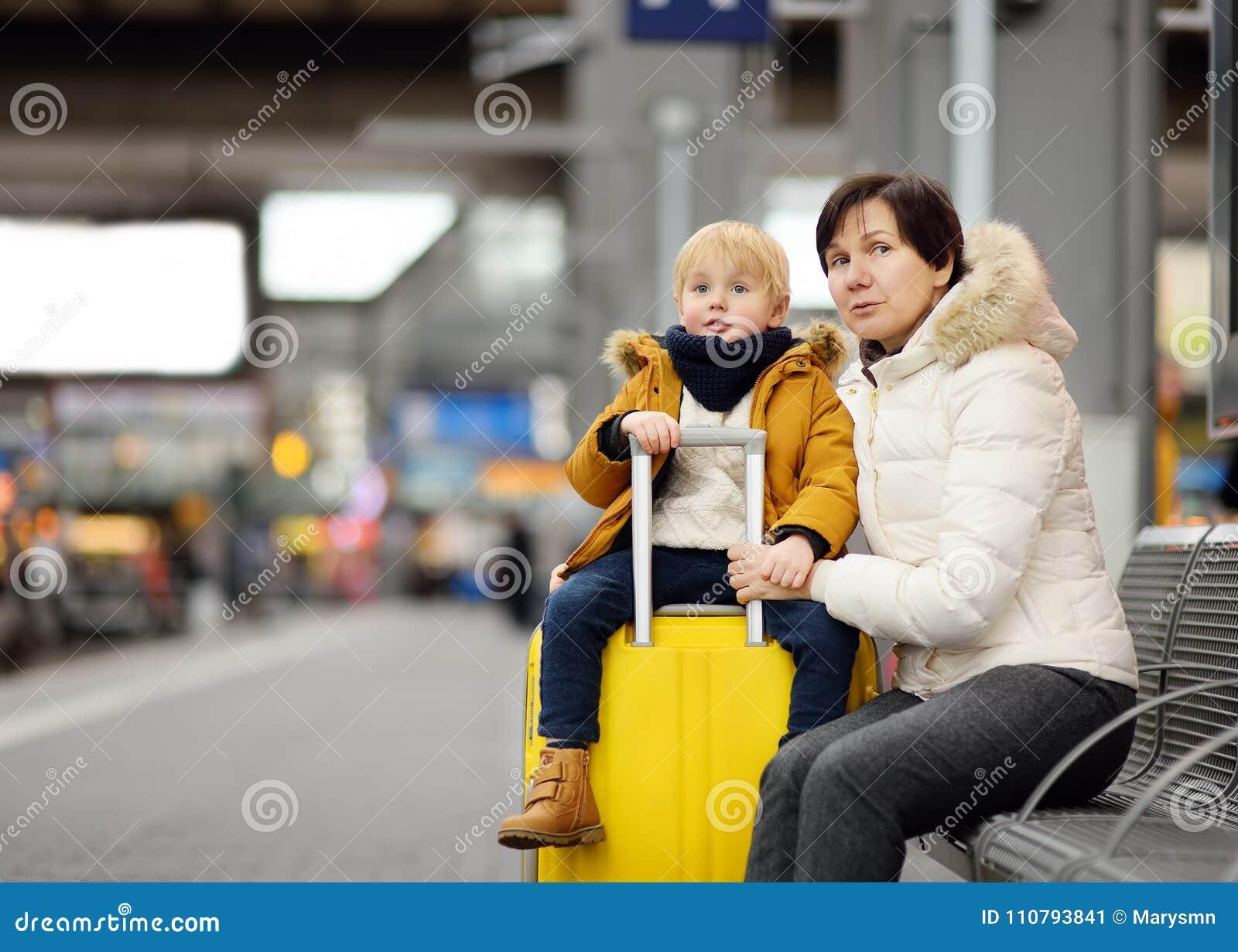 Leuk weinig jongen en zijn grootmoeder/moeder het wachten sneltrein op stationplatform